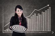 Stock Illustration of businesswoman hold bull's eye on growing bar chart