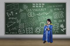 Asian girl graduate holding book in class Stock Illustration