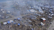 Aerial following a road t through destroyed villages Stock Footage