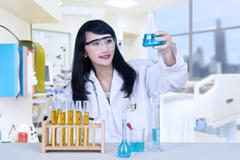 Beautiful female doctor analysing chemical in hospital Stock Photos