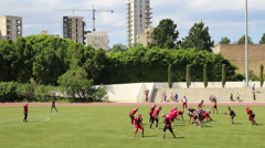 A football team practices on the athletic field at the American University Of Stock Footage