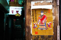Poster of Chinese money god on wall of residential building, Hong Kong Stock Photos