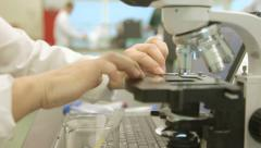 Tracking shot of lab technician placing slide under microscope - stock footage
