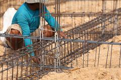 worker prepare steel rod for construction job - stock photo