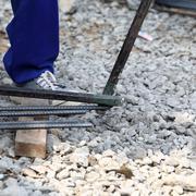 worker bending steel for construction job - stock photo