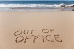 Out of office - written in sand on a beach - stock photo