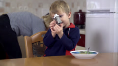 Boy at lunch playing with scraper - stock footage