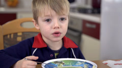 Close up of young boy eating soup with noodles - stock footage