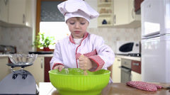 Stock Video Footage of Liquid ingredient falling to bowl while kid mixing