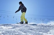 Stock Photo of Unidentified snowboarder snowboarding down the slope in the Austrian Alps