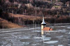 Abandoned church in a mud lake. natural mining disaster with water pollution Stock Photos