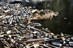 Lake water pollution with garbage - stock photo