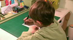 Little boy writing, child works at his desk, school boy doing homework Stock Footage