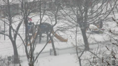 Heavy snow in the city, snowstorm, bad weather, children in the park, blizzard Stock Footage
