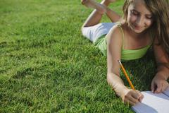 smiling nine year old girl sitting on grass, writing in notebook - stock photo