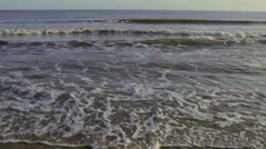 Small gentle waves rolling onto sandy beach - stock footage