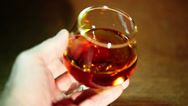 Stock Video Footage of Man's hand with a glass of cognac, brandy close up