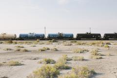 Tavaroiden juna juna radalla kulkee aavikon. Kuvituskuvat