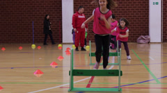 Children running over obstacles  in sports hall,sports recreation - stock footage