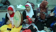 Traditionally dressed Indonesian females pray and chant muslim songs Stock Footage