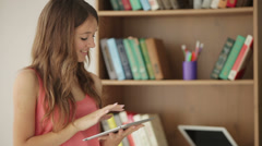Cheerful girl standing beside bookcase using touchpad looking at camera  Stock Footage