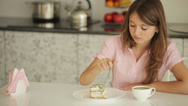 Stock Video Footage of Cheerful girl sitting at table eating cake looking at camera and smiling