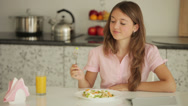 Stock Video Footage of Charming girl sitting at table eating salad using touchpad and smiling at camera