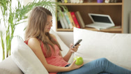 Stock Video Footage of Cute girl relaxing on sofa using mobile phone eating apple looking at camera