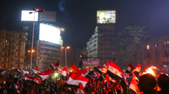View from the ground as protestors chant and wave flags at a large nighttime - stock footage