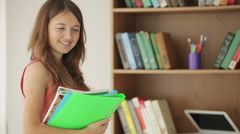Happy girl standing beside bookcase holding workbooks and smiling at camera Stock Footage