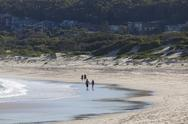 Stock Photo of two couples walk on a beach. fingal bay. port stephens. australia.