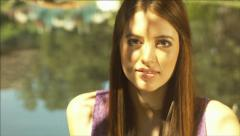 Face, head and shoulders of a beautiful girl not smiling by a pond Stock Footage