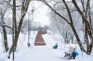 Stock Photo of winter promenade for walking with a bench and a lantern