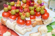Stock Photo of canapes with ham tomato and olive on a toothpick
