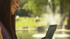 Close up profile of a beautiful girl using a digital tablet at a table outdoors - stock footage