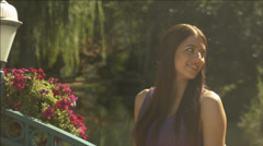 Beautiful girl looks over shoulder, then to camera in lovely outdoor setting Stock Footage