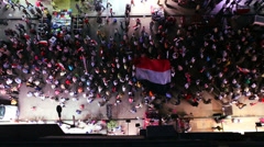 View from overhead looking straight down on protestors marching in the streets - stock footage