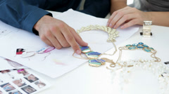 Design team looking at costume jewelry and talking - stock footage