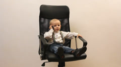 Little boy kid speaking business at mobile phone on office chair Stock Footage