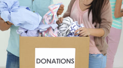 Team of smiling workers going through donation box of clothes Stock Footage