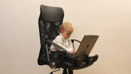 Stock Video Footage of Little businessman child work hard at laptop on office chair