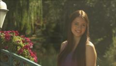Beautiful girl looking away, to camera, then down in a lovely outdoor setting Stock Footage