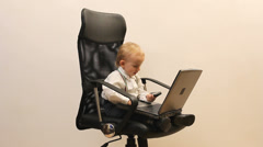 Funny little child play the manager, enjoy to work, phone, laptop, office chair Stock Footage