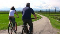 Senior man and young girl riding bikes downhill on a country road - HD1080i - stock footage