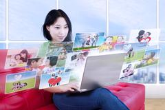 Asian female looking at online photos in apartment Stock Illustration