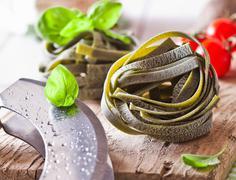 uncooked ribbon tagliatelle pasta - stock photo