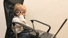 Busy little bussinessman with notebook and mobile phone on office chair Stock Footage