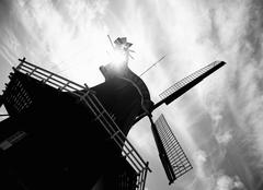 tilted windmill with sun flare - stock photo