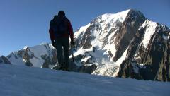 Mountain climber walks on a glacier; in background the beautiful view on Mont Stock Footage
