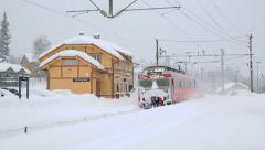 Commuter train arriving station in snow weather Stock Footage